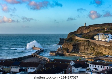Stormy weather at Portreath, Cornwall, UK with waves breaking over the Monkey Hut and the Pepperpot visible on the high cliff.