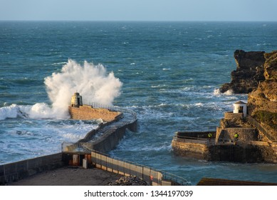 Stormy weather at Portreath, Cornwall, UK with waves breaking over the Monkey Hut which was originally built as a shelter for the harbour pilots.