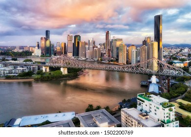 Story bridge in Brisbane city over Brisbane river in front of high-rise business towers and apartment buildings at sunrise in elevated aerial view.