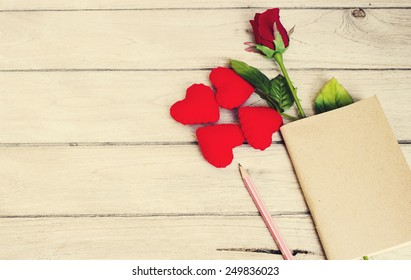 story love,Hearts, roses, pencil and book on wood