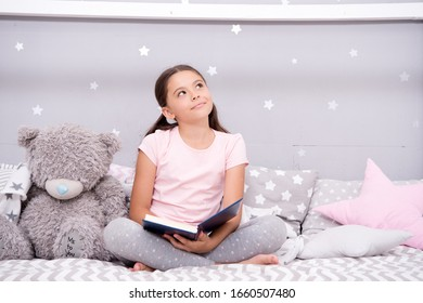Story that grabs imagination. Little girl read and imagine. Cute dreamer with book and toy. Kids imagination and fantasy. Reading feeds imagination. Inspiring child imagination.