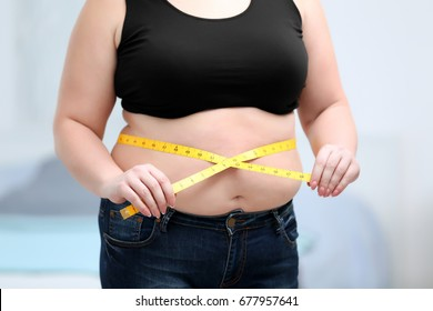 Stout adult woman with measuring tape at home. Weight loss concept