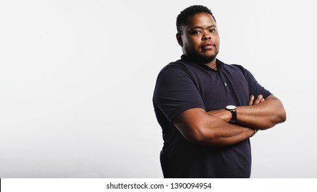 Stout african man standing against white background looking at camera. Portrait of a man standing with arms folded.