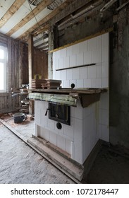 Stove building in process: traditional cooking stove of glazed white tiles being built into old unrenovated room. Photographed in Estonia, Europe. Wide lense.