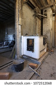Stove building in process: traditional cooking stove of glazed white tiles being built into old unrenovated kitchen. Photographed in Estonia, Europe. Wide lense.