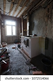 Stove building in process: traditional cooking stove of glazed white tiles being built into old unrenovated house. Photographed in Estonia, Europe. Wide lense.