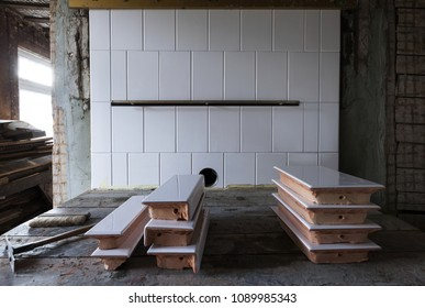 Stove building in process: traditional cooking stove of glazed white tiles, photographed in Estonia, Europe. Focus on tile wall, back.