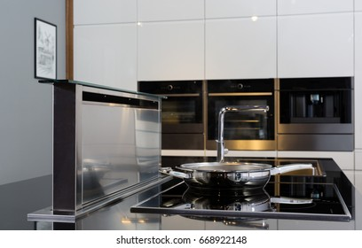 Stove and cooking hood on modern minimalism style kitchen. Moveble hood coming from the countertop. Combination of materials.