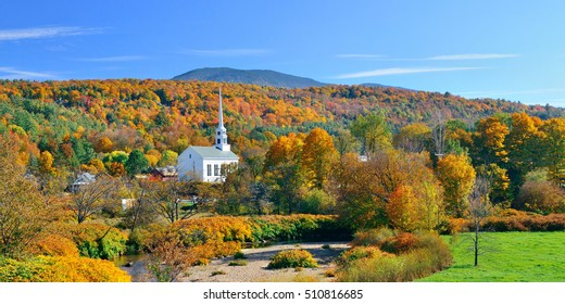 Stowe panorama in Autumn with colorful foliage and community church in Vermont