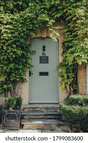 Stow-on-the-Wold, UK - July 10, 2020: Plant-framed doorway entrance to a traditional limestone house in Stow-on-the-Wold, a market town in Cotswolds, UK, built on Roman Fosse Way.