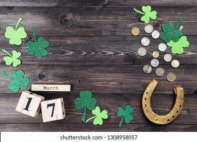 St.Patrick's Day. Golden horseshoe with clover leafs, wooden calendar and coins