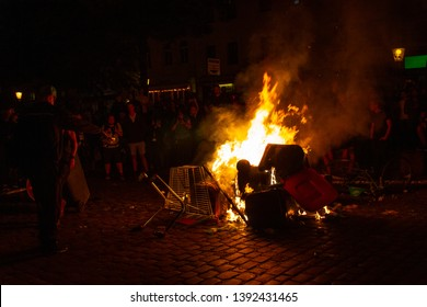 """ST.PAULI/HAMBURG - GERMANY, July 6, 2017: Protestant throwing a garbage bin into a burning street blockade in front of the """"Rote Flora""""."""