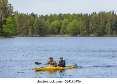 St.-Peterburg, Russia - 08 June 2017: People in a yellow kayak floating on the lake