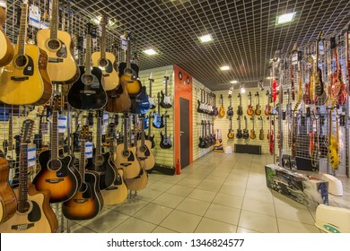 St.Petersburg - December 6, 2018 A row of different electric guitars hanging in a modern musical shop