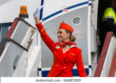 St.Petersburg, Russia - 10 aug. 2017: Beautiful charming Stewardess dressed in official red uniform of Aeroflot Russian airlines on the moving ramp near the plane in airport. Smiling cabin crew.