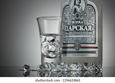 St.Petersburg, Russia - December 2018 - Bottle of cold vodka Czar's with ices and shot glass on a grey background with reflection. Premium vodka.  Produced in Russia. Original russian recipe