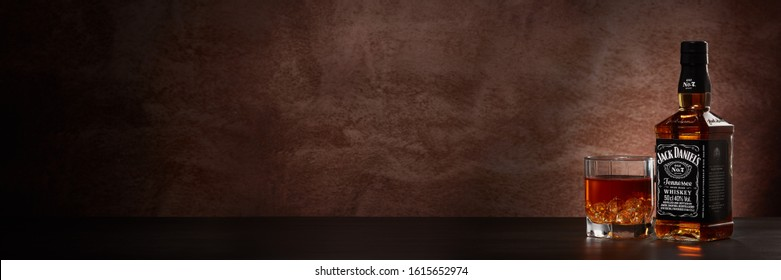 St.Petersburg, Russia - December 2019 - Bottle of Jack Daniel's whiskey and glass with drink and ice on wooden table on brown background with copy space. Extra wide panorama banner background