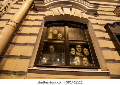 ST.PETERSBURG, RUSSIA - February 29, 2016 : Masks of human faces are watching into the street from a dark window.Window of wax figure museum.The ghost house.