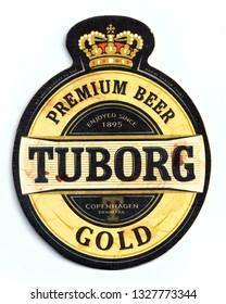 ST-PETERSBURG, RUSSIA - MARCH 3, 2019 - Vintage stained coaster (beer mat) with ad of Tuborg Gold beer.  Isolated on white background