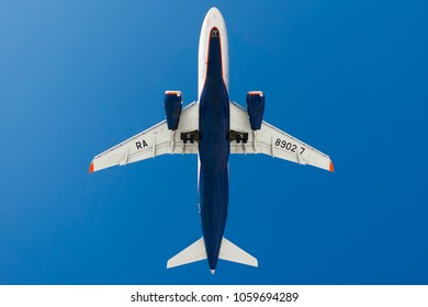 St.Petersburg/ Russia - March 31 2018: Sukhoi Superjet 100 of Aeroflot Russian airlines on a blue sky background. Bottom view landing at Pulkovo airport. composition photo. flying overhead.