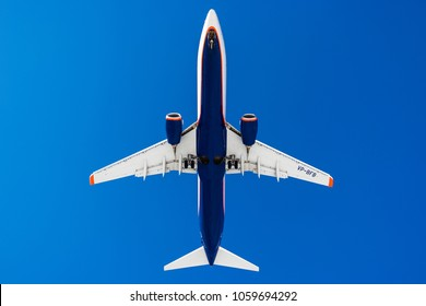 St.Petersburg/ Russia - March 31 2018: Boeing 737 of Aeroflot Russian airlines on a blue sky background. Bottom view landing at Pulkovo airport. composition photo. flying overhead.