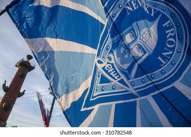 """ST.PETERSBURG, RUSSIA, MAY 25, 2015: Fan holding a flag with symbols of the football club """"Zenit"""" and the fans club """"Nevsky Front"""" at the center of Saint Petersburg city, Russia"""