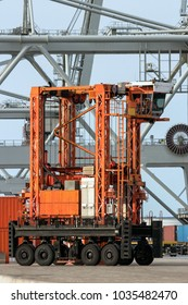 Straddle carrier moving cargo containers in a shipping terminal.
