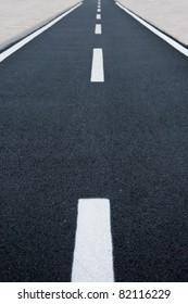 Straight asphalt bicycle road vanishing in perspective