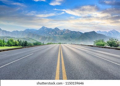 Straight asphalt highway and green mountain nature landscape at sunset