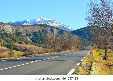 Straight asphalt mountain road in french alps on a clear day. Ecrins massif