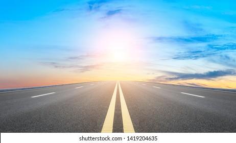 Gerader Asphaltweg und Sonnenuntergang