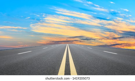 Straight asphalt road and sunset sky