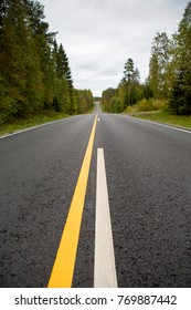 Straight asphalt road with yellow and white marks.