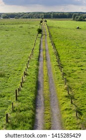 A straight country road with fence and fields seen from above.