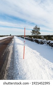 Straight country road with a red snow stake by roadside