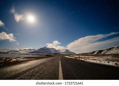 Landstraße unter dem Mondlicht mit dramatischen Wolken und Sternenhimmel, Island