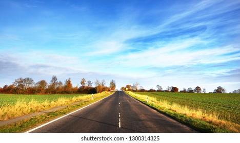 Straight countryside asphalt road on a clear autumn day