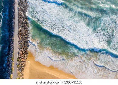 A straight down view of the Breakwall at Nobbys Beach - Newcastle Australia with rough surf pounding onto the shoreline. Nobbys BEach - Newcastle - NSW Australia