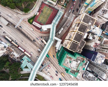 Straight down view of a foot bridge over a city street in a residential district of Kowloon city in Hong Kong, China
