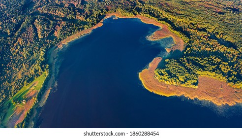 Straight down view of Krymne Lake. First sunlight glooving the shoure of fishing lake. Bright morning scene of Shatsky National Park, Volyn region, Ukraine, Europe. Aerial landscape photography.