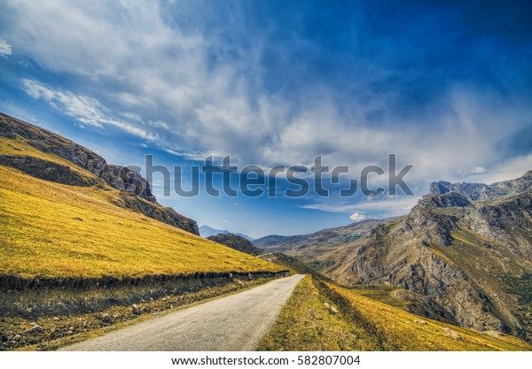Straight empty highway leading into Xinalig village. Beautiful landscape of big Caucasus mountains and road country road with blue cloudy sky and yellow grass. Azerbaijan Guba nature