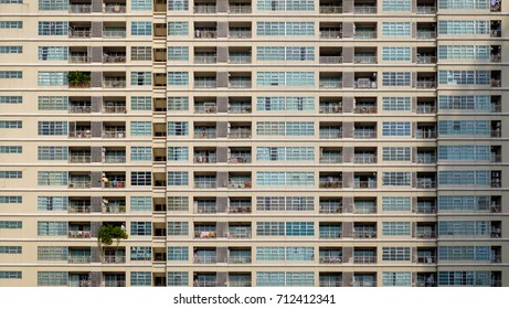 Straight facades of condominium buildings. Concept of dense population, overpopulation, living in modern style residence / high rise condominium.