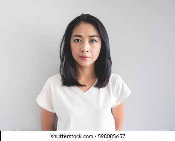 Straight face portrait of Asian woman in white t-shirt.