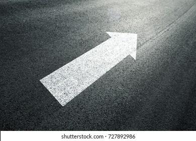 Straight forward arrow direction sign on the sunny asphalt ground.