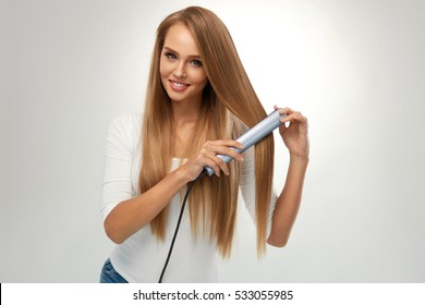 Straight Hair. Beautiful Smiling Woman Straightening Healthy Long Blonde Hair With Flat Iron, Hair Straightener. Portrait Gorgeous Girl Model Ironing Hair. Beauty, Hairstyle Concept. High Resolution