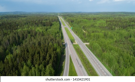 Straight highway through deep forest aerial view. Bright summer image. FInland