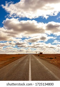 Straight and lonely road with a cloudy sky