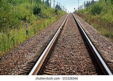Straight modern railway perspective with gravel, poles, green grass and trees