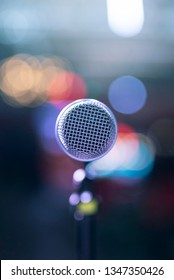 Straight on angle of a singer's microphone on a stage set for an indoor concert.