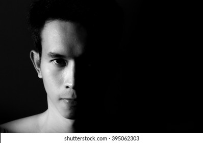 Straight on black and white head shot of a man looking into camera with half his face shadowed on a black background